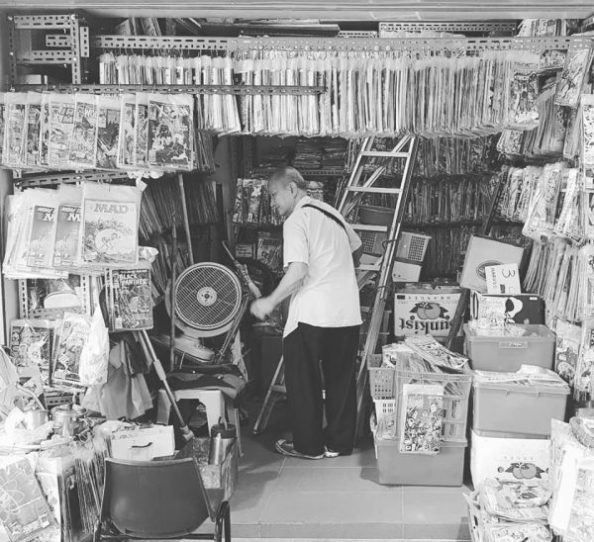 Mr. Low working inside his modest comic book shop, Silver Kris