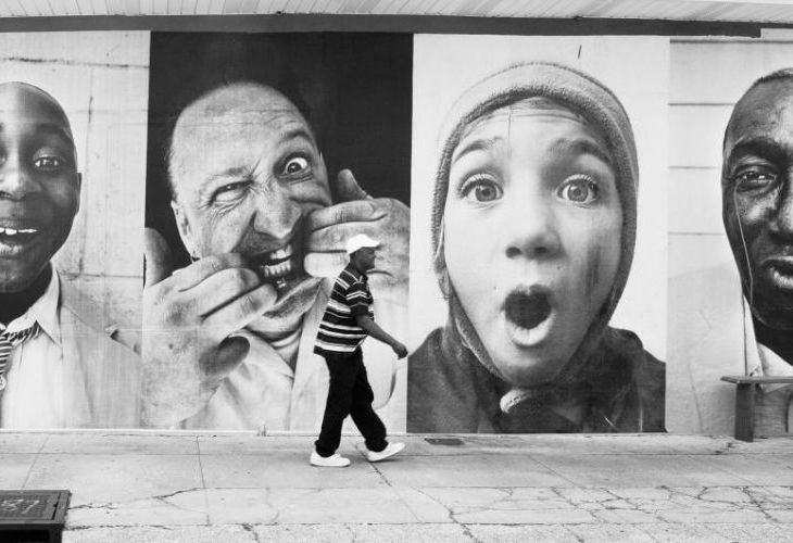 A man walks past the inside out photography project in the black and white image