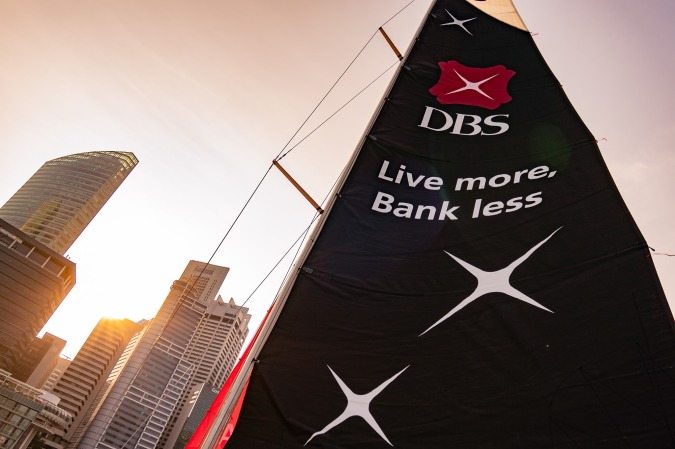 """From a tall building hangs a flowing banner with DBS bank logo and their famous tagline, """"Live more, Bank less."""""""