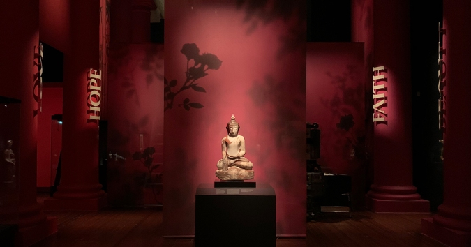 Image reveals an 18th century marble sculpture of a Seated Buddha on display at Faith Beauty Love Hope - Our Stories, Your ACM exhibition at the Asian Civilisations Museum.