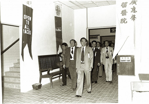 An old photograph of Kwong Wai Shiu Free Hospital in 1974 with banners inviting patients of all races.